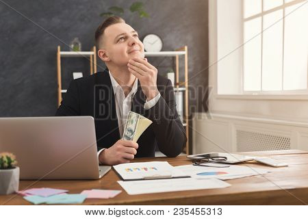 Thoughtful Male Financier Sitting At Office Table, Holding Money In Hands And Dreaming. Man Counting