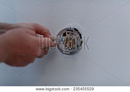 Electrician Man At Work On Switches And Sockets Of A Residential Electrical System.