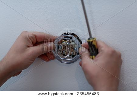 Electrician Man Installing New Electrical Switches Using Pliers During The Renovation Of The House C