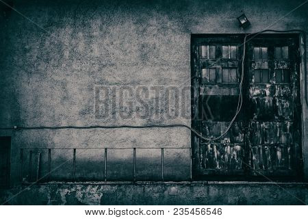 Giant Door Of Old Abandoned Building With Downed Wire Of Street Light. Empty Dark Wall. Sinister Urb