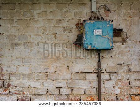 Old And Dangerous Rusty Blue Electric Fuse Box On Grunge Brick Wall.