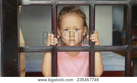 Portrait Of Cute Little Girl Looking Out The Window, From Outside Shot. Sad Child Looks At Camera Th
