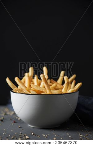 some appetizing french fries served in a white ceramic bowl, placed on a gray rustic wooden table, against a black background with some blank space on top