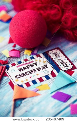 a curly red hair wig, a red clown nose and the text happy circus day in a simulated admission ticket made by myself, on a blue rustic wooden surface full of confetti
