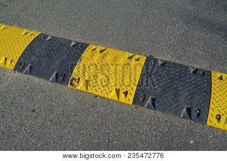 speed bump on asphalt road, speed limit poster