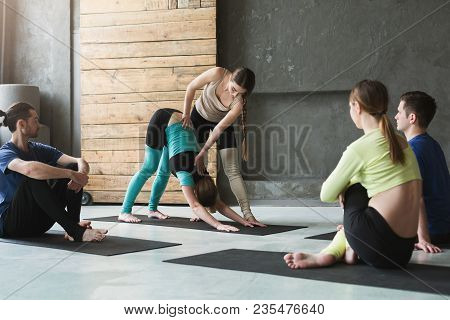 Yoga Teacher And Beginners In Class, Making Asana Exercises. Healthy Lifestyle In Fitness Club. Stre