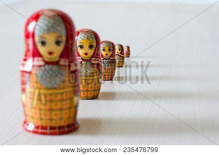 Five Red Matryoshka. Long Shadows. Selective Focus. Close Up