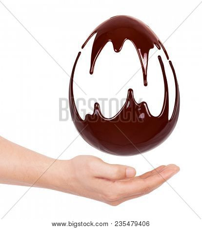 Chocolate egg in a hand. Melted chocolate syrup on a white background. Liquid chocolate on a white background.