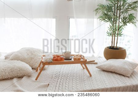 Breakfast On Wooden Tray. Blank Cup, Croissants, Donuts Standing In Front Of Big Window On Knitted C