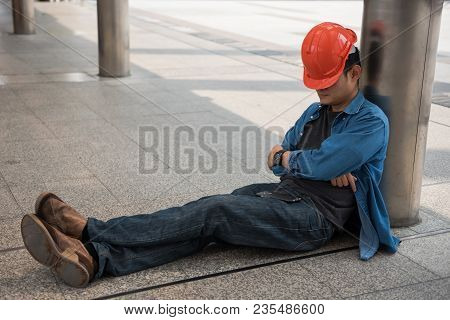 Lazy Engineer With Orange Helmet Sleeping At Construction Site In Modern City. Engineering Man Take