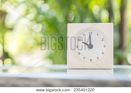 Closeup White Clock Show Ten O'clock On Blurred Marble Table In The Garden Background
