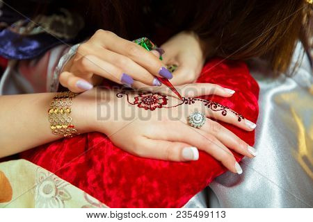 Henna Design Tattoo. Women Applying Henna Tattoo On Women Hands. Artist Applying Henna Tattoo On Bri