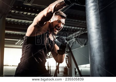 Bearded Male Boxer Training With Punching Bag In Dark Sports Hall. Young Tattoed Boxer Training On P
