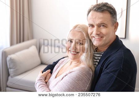 Portrait of happy pensioners at home