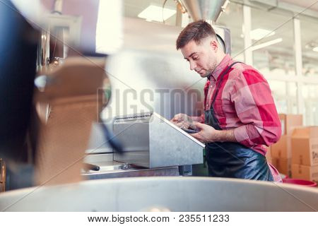 Photo of businessman with phone at computer of industrial machine
