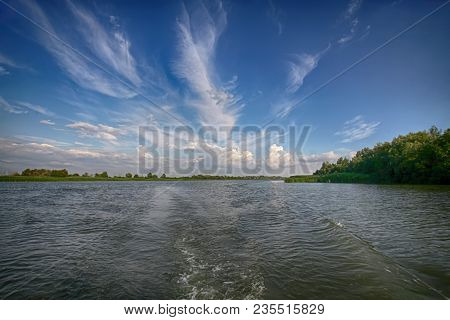 A beautiful view of the river surface and the reflection of the sky from the side of the boat going along the waves poster