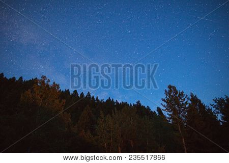 Long Exposure Photo Of Night Sky With Faint Milky Way And Streak Of Light. Remote Forest Area.