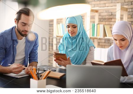 Male student and his Muslim classmates in library