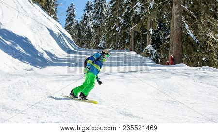 Image Of Man Riding Snowboard From Snowy Hill On Winter Day