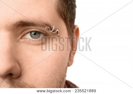 Young man with pierced eyebrow on light background, closeup