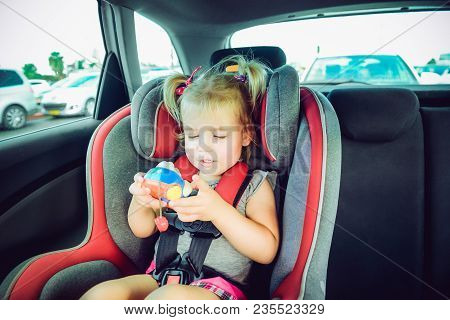 Blondy Baby Girl Fastened With Security Belt In Safety Car Seat And Plaing With Toy. Child In Auto B