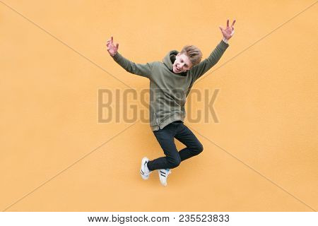 Happy Young Man Jumping Against The Background Of An Orange Wall. The Leap Of An Emotional Student O
