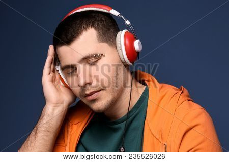 Young man with pierced eyebrow listening to music on color background