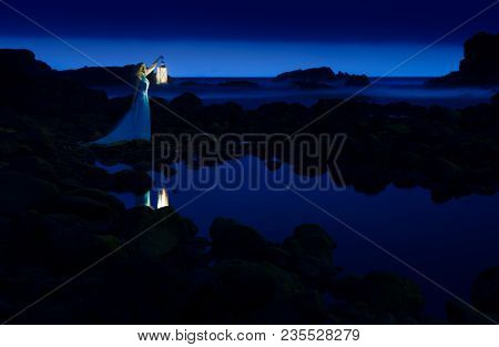 Dark Night, Blue Sea And Sky, Blonde Woman In Long Dress With Lantern
