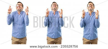 Middle age handsome man with crossed fingers asking for good luck over white background