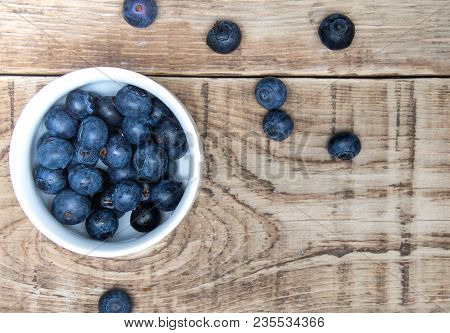 Fresh Bilberry Berry In White Cup On Wooden Table