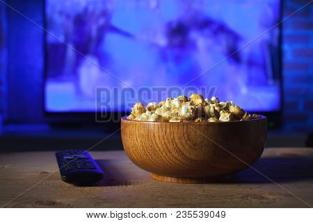 A Wooden Bowl Of Popcorn And The Tv Remote In The Background The Tv Works. Evening Cozy Watching A M