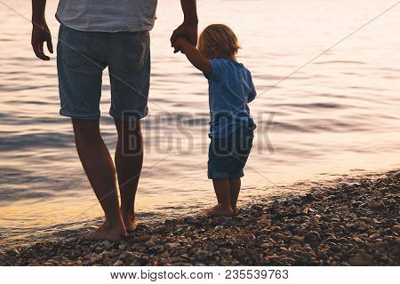 Father And Son Back Silhouettes Walking By The Sea. Man And Kid Boy Playing Together Outdoors On A S