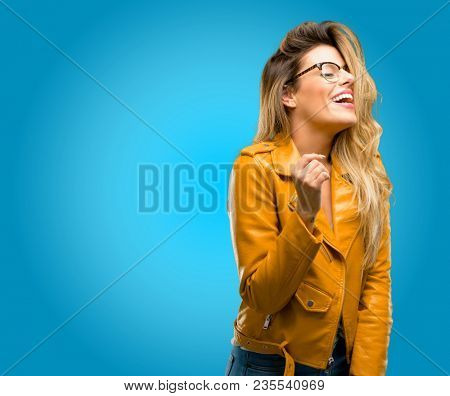 Beautiful young woman confident and happy with a big natural smile laughing, natural expression, blue background