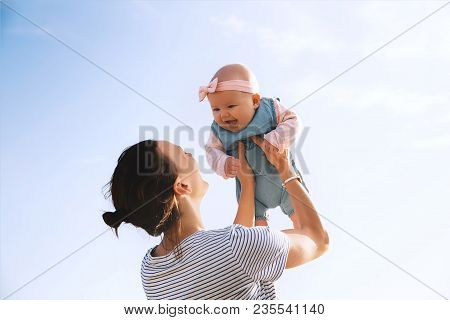 Young Mother Throws Up Baby In The Sky, Summer Outdoors. Happy Mom And Cute Smiling Baby Girl. Posit