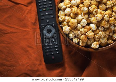 Wooden Bowl With Sweet Popcorn And Tv Remote On Orange Bedding. Top View With Copy Space. Snacks And