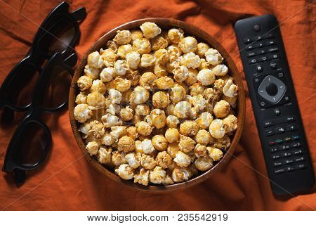 Wooden Bowl With Sweet Popcorn, Tv Remote Control And 3d Glasses On Orange Bedding. Top View. Snacks