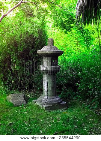 Japanese Stone Lantern In The Style Of Feng Shui On The Green Background Of Leaves