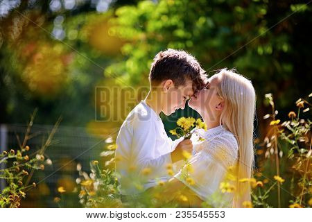 Mother And Son Having Fun. Son Giving Flowers To His Mother And Kissing Her. Outdoor Shot.