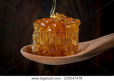 Drizzling Honey Over Comb Sitting In Wooden Spoon