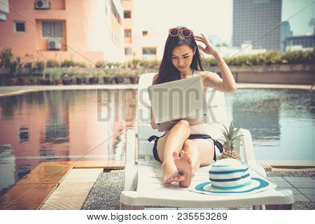 Young Asian Girl Working At Swimming Pool. Freelance Female Resting On Sunbed Enjoying Travel On Vac