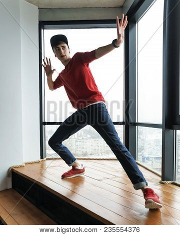 Teenager In Red Sweater And Baseball Cap, Jeans And Sneakers Dances By Window In Dance Studio. Moder