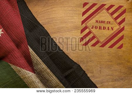 Flag Of Jordan From A Rough Fabric On A Wooden Background And Stamp Made In Jordan