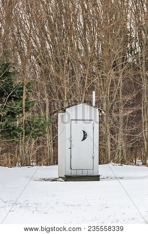 Old White Outhouse With A Crescent Moon On The Door On A Winter Day