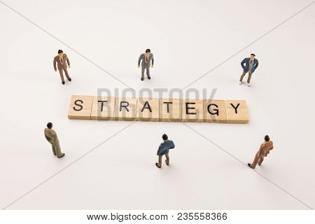 Miniature Figures Businessman : Meeting On Strategy Word By Wooden Block Word On White Paper Backgro