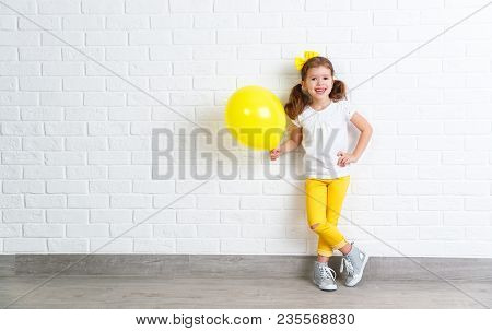 Happy Funny Child Girl With Yellow Air Balloon Near An Empty Brick Wall