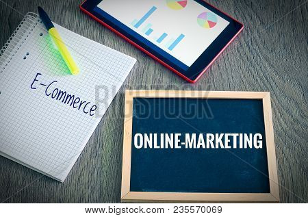 Plate With The Inscription Online-marketing Ande-commerce With A Tablet Graphs And Statistics And Bl