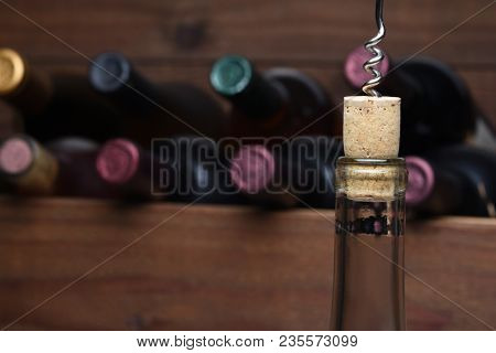 Pulling a cork: Closeup of a wine bottle with the cork partially pulled out. An out-of-focus wood case of wine is in the background.