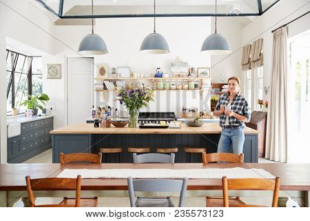 Young woman standing in an open plan kitchen dining room