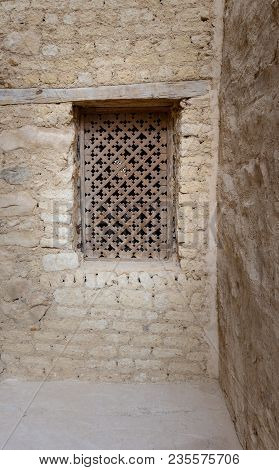 Ancient Wooden Window With Geometrical Pattern Based On The Christian Cross On External Brick Stone