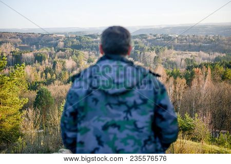 Adult Male In Jacket Observes Beautiful Spring Landscape In Sunset During Hiking